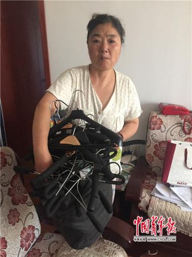 8月16日,刘伶利逝世第三天,她的母亲刘淑琴整顿女儿患病时期摆摊用的衣架。国家青年报·中青在线记者 章正/摄