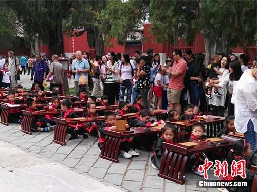 """9月1日,有小学在北京孔庙举行入学""""开笔礼""""仪式,小学生穿着汉服,周围还有家长。中新网记者 宋宇晟 摄"""