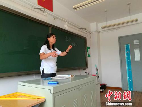 高二语文老师王楠用手语为学生们上课。 中新网记者 张尼 摄