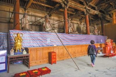 游客来到正在修复中的下寺后佛殿参观。