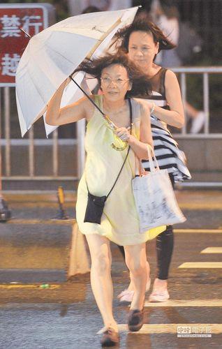 """遭到""""鲇鱼""""飓风的作用,台北地域9月26日天黑以后风势转强,路人撑着伞慢步超出斑马线。来历:台湾《国家时报》"""