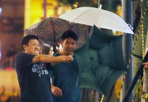 """中度飓风""""鲇鱼""""直扑台湾,台北市9月26日天黑后雨势渐强,随同突来的强阵风,让开下行人雨遮时时着花,很是难堪。台湾《结合报》记者胡经周/拍照"""