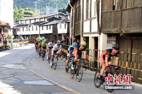 加入环泉州湾国际自行车赛的选手通过德化县赤水古街。 许华森 摄