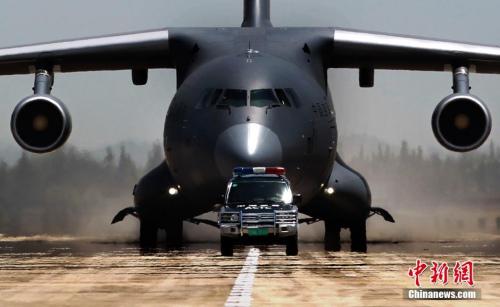 图为在引导车的带领下,运-20飞机缓缓滑向停机坪。中新社发 刘畅 摄
