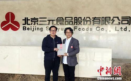 IAI国际广告奖执行主席刘广飞(右)向北京三元食品股份有限公司总经理陈历俊(左)赠送《2016IAI广告作品与数字营销年鉴》