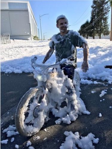 路人闯入泡沫海洋中,单车与人都沾满白色泡泡。