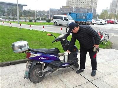 11月20日,陈思骑电动车巡江。由于每次出去就是一整天,他都会自备一个水壶。