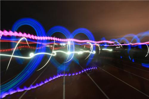 """10月29日,景德镇陶瓷大学""""迷马""""荧光夜跑现场,光影交织,有限梦境。夏哲雨/摄"""