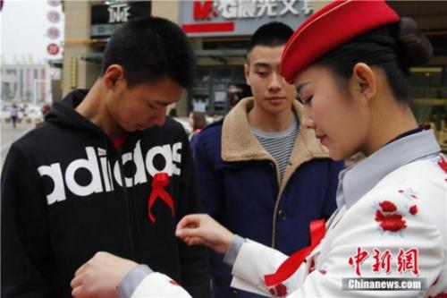 """资料图:四川西南航空职业学院的10名准空姐、准空少以""""艾滋病患者""""的身份,向过往的行人索要拥抱,以此进行""""防艾""""宣传。毛成山 摄"""