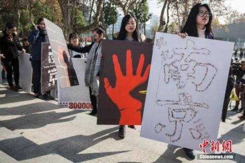 2016年12月5日,南京艺术学院的大门生展现国度公祭日主题海报著作。中新社记者 泱波 摄