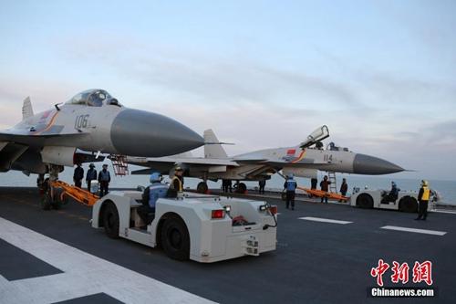 中国海军日前组织实施了航母编队实际使用武器演习。演习在渤海某海域展开,共动用辽宁舰等各型舰艇数十艘、飞机数十架,发射空对空、空对舰和舰对空等各型导弹十余枚。演习中,辽宁舰与数艘驱护舰组成编队,先后开展了建立侦察预警体系、空中拦截、对海突击和防空反导等科目演练,多批次歼―15舰载战斗机挂载实弹,飞赴演习海空域实施打击行动。图为两架舰载战斗机进行起飞前准备工作。发 莫小亮 摄