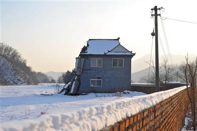 12月14日下午,残存的岫岩县偏岭镇丰富村村部二层楼房还在讲述着那次泥石流灾害的惨烈。