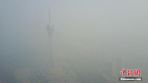 连日以来河南郑州被雾霾笼罩,12月18日,河南郑州仍是雾霾围城,图为隐身于雾霾之中的河南广播电视发射塔。王中举 摄