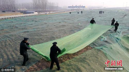 12月16日,北京,大兴区安定镇京台高速安定出口处,城管队员正在苫盖建筑垃圾。图片来源:视觉中国