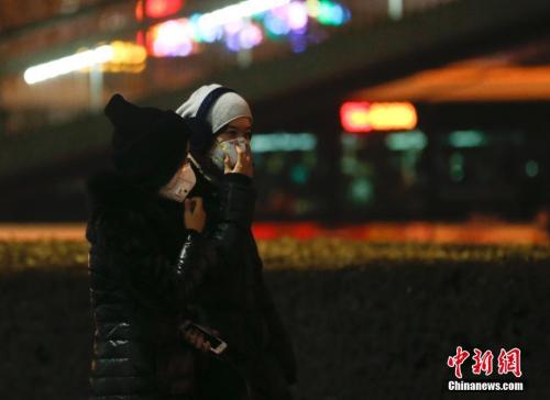 12月16日,北京民众戴防雾霾口罩出行。中新社记者 杜洋 摄