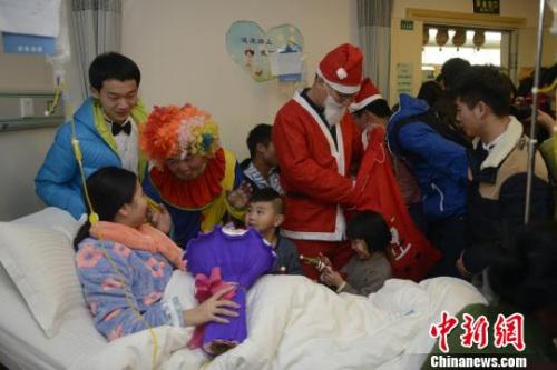 资料图:医生与工作人员扮成圣诞老人和小丑为患者送礼物。 彭露 摄