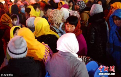 资料图 山东省济南市,多名农民工聚集在路口处,站在寒风中寻找工作。 御宁 摄 图片来源:视觉中国