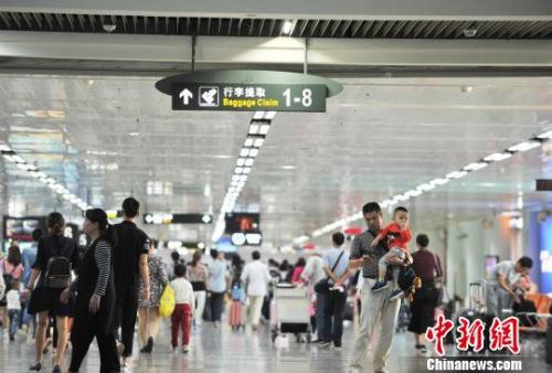 资料图 图为海口美兰机场到达大厅迎来大量进港旅客。 楚洪雨 摄