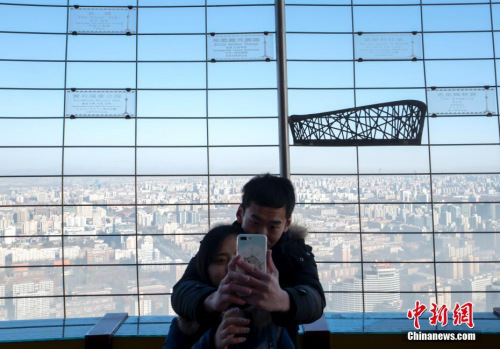 1月2日,雾霾暂别北京,蓝天重现,一对年青人登上地方电视塔观景台自拍美景。 中新社记者 侯宇 摄