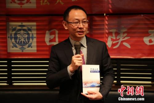 图为国家驻日使馆总领事王军向侨胞引见使馆新编印的《国家百姓客居日本手册》。 尹法根 摄