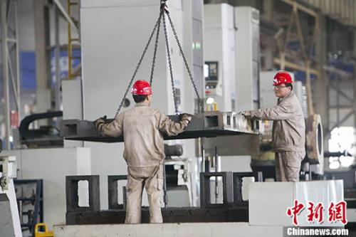 资料图:山西太重工人正在吊装机械配件。 中新社记者 张云 摄