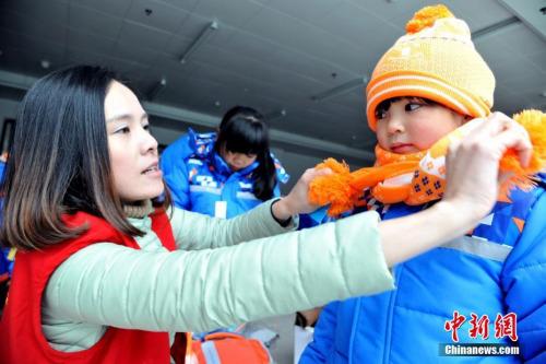 """12月15日下午,江西省万载县龙湖公园,万载义工联合会的志愿者们向165名贫困学生发放由壹基金提供的""""爱心温暖包"""",温暖包内有手套、围巾、棉衣等御寒物品。随后志愿者们与孩子们一起做游戏,孩子们灿烂的小脸洋溢着喜悦,欢笑声回荡在这个""""温暖的冬天""""。图为志愿者为孩子系上围巾。 邓龙华 摄"""