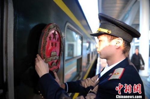 每次国际列车出发前,都要将国徽擦干净。 蒋雪林 摄