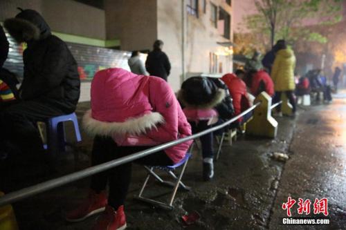 资料图:2016年4月6日,在西安市丈八四路缤纷南郡小区内的幼儿园后门附近,家长排队等待报名。图片来源:视觉中国
