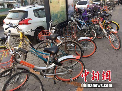 """两辆单车""""加塞""""停放,占用了部分公共道路。 吴涛 摄"""