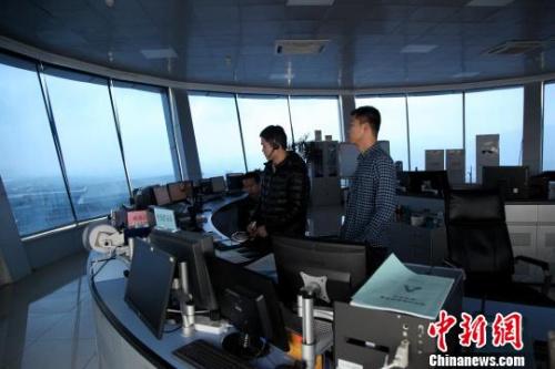 """图为塔台管制室内,管制员正在""""指挥""""飞机。 李雨浓 摄"""
