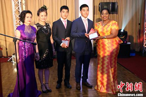 """图为邦吉・祖马(右一)与全非洲华人妇女联合总会会长朱怡苑(左一)为表现出色的华人子女颁发""""育才""""奖学金。 记者 宋方灿 摄"""