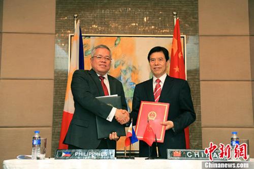 钟山(右)与洛佩兹(左)在会后签署会议纪要并出席新闻发布会。记者 钟欣 摄