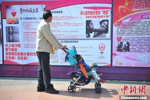 资料图:市民在广西南宁市民族广场观看反家暴资料。 记者 胡雁 摄