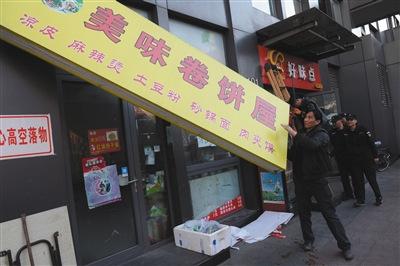 昨日下午,丰台区食药监局执法人员对涉嫌违法经营的店铺招牌进行拆除。新京报记者 吴江 摄