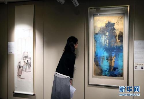 3月14日,一位记者在香港苏富比春拍记者会上观看张大千的泼墨泼彩山水画作《��霍瑞霭》。香港苏富比将于4月4日举行中国书画专场拍卖会,呈献逾300幅中国近现代书画佳作,总估值约1.6亿港币。 新华社记者 李鹏 摄