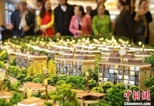资料图。购房者在北京亦庄某楼盘进行买房或咨询。