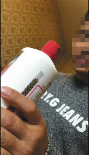 2月14日,张建拿出一瓶假茅台酒样品给记者展示