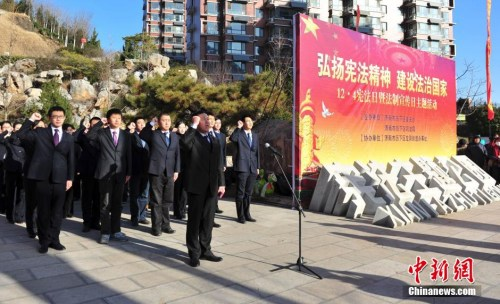 """资料图:2014年12月4日,济南历下区公务员代表在中国首个""""宪法主题公园""""集体向宪法宣誓。 中新社发 张勇 摄"""