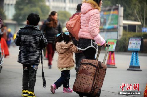 资料图:2015年2月5日,2015年春运第二天,江苏扬州市汽车西站迎来客流高峰,图为家长带着孩子在江苏扬州市汽车西站候车。 孟德龙 摄