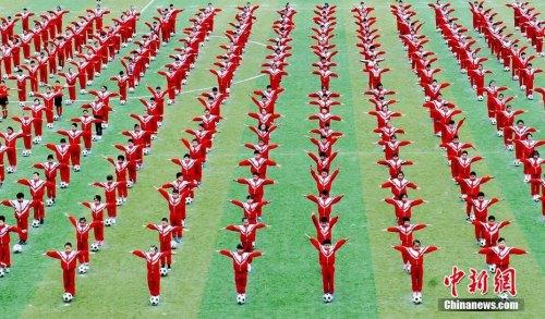 资料图:2016年11月2日,江西省德兴市某小学上千名小学生在操场上开心跳起足球舞。卓忠伟 摄
