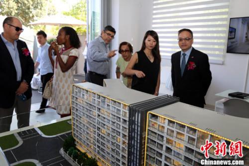 图为中国驻约翰内斯堡副总领事屈伯勋(右一)参观公寓大楼沙盘。记者 宋方灿 摄