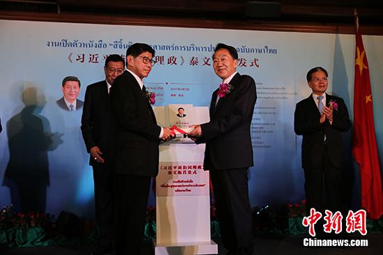 中宣部副部长、国务院新闻办主任蒋建国(右)向泰国副总理威沙努赠送该书。 中新社记者 王国安 摄