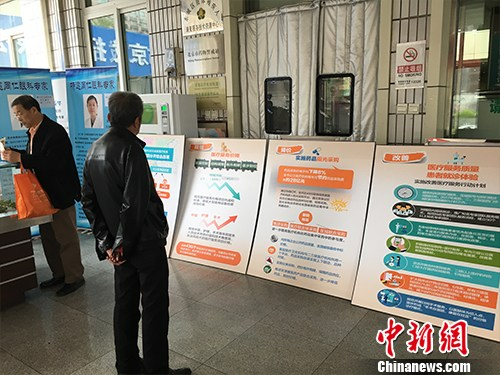 北京普仁医院外,有人在看医改宣传板。