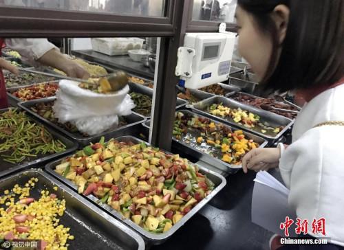 资料图:学生在校食堂窗口前买餐。图片来源:视觉中国