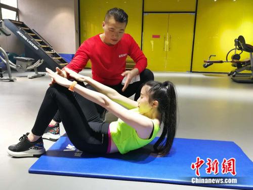 健身教练在健身房指导学员 记者 张尼摄