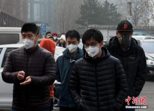 资料图:北京街头,民众出行时佩戴口罩应对雾霾。记者 侯宇 摄
