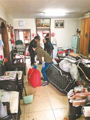 社区工作人员从老人家中清出众多垃圾 供图/双晨社区