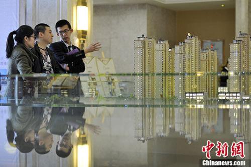 资料图 置业顾问向民众推荐商品房户型。 中新社记者 韦亮 摄