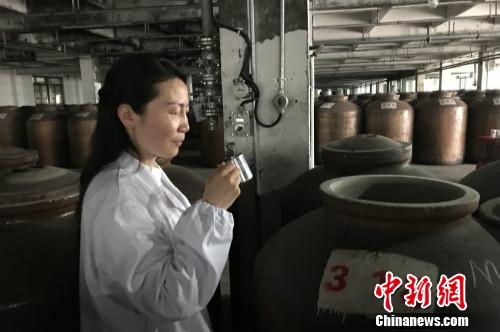 高玲在品尝装在酒缸里的原酒。<a target='_blank' href='http://www.chinanews.com.5888caipiao.com/' >中新网</a> 种卿 摄