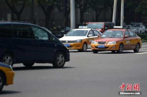 资料图:行驶在路上的传统出租车。记者 金硕 摄